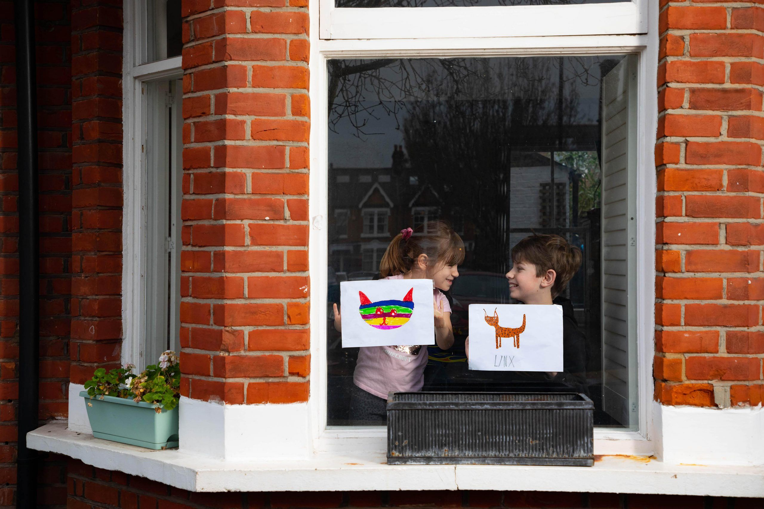 Artwork depicting animals created by left to right Romey and Iggy is displayed in the windows of a row of houses in Acton London. Photo David Parry PA Wire 2